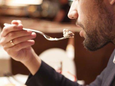 Mann som spiser mat i restauranten